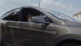 Mano d'ondeggiamento della ragazza alla macchina fotografica durante l'automobile che guida indietro video d archivio