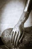 Mano dalla statua dorata di Buddha in in bianco e nero Immagine Stock