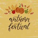 Mano de Autumn Festival dibujada poniendo letras a frase en fondo amarillo y de madera libre illustration