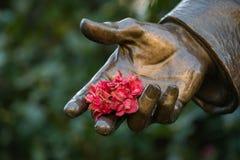 Mano de bronce de la estatua que sostiene las flores Foto de archivo libre de regalías