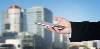 Mano de Businessmans que sostiene Smartphone con la ciudad del negocio y los edificios corporativos en fondo imagenes de archivo