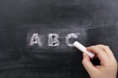 Mano de Childs que escribe ABC en la pizarra Imagen de archivo libre de regalías