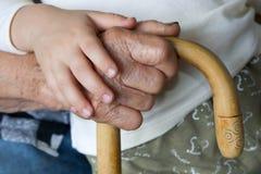 Mano de la abuela y del nieto Imagen de archivo libre de regalías