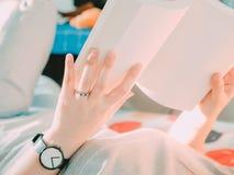 Mano de la belleza con el anillo de bodas de la mujer del inconformista que miente en los wi de la cama Fotos de archivo libres de regalías