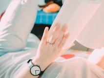 Mano de la belleza con el anillo de bodas y el reloj negro de la mujer del inconformista Imágenes de archivo libres de regalías