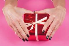 Mano de la chica joven con los clavos negros en la actual caja roja con el arco blanco en fondo rosado Foto de archivo