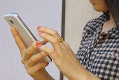 Mano de la chica joven que sostiene el teléfono móvil Foto de archivo