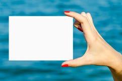 Mano de la chica joven que sostiene la tarjeta en blanco blanca Imagenes de archivo