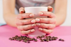 Mano de la chica joven que sostiene la taza de café y de granos de café en el escritorio rosado Imagen de archivo libre de regalías