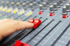 Mano de la consola de mezcla del control del hombre de un sistema de alta fidelidad grande el equipo de audio fotos de archivo libres de regalías