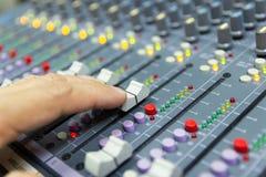 Mano de la consola de mezcla del control del hombre de un sistema de alta fidelidad grande el equipo de audio foto de archivo