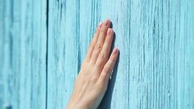 Mano de la diapositiva de la mujer contra puerta de madera azul-coloreada en la cámara lenta Superficie femenina del tacto de la  metrajes