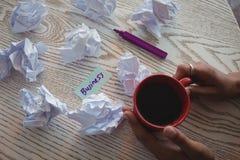 Mano de la empresaria que sostiene el café por los papeles arrugados en el escritorio en oficina Imagen de archivo libre de regalías