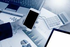 Mano de la empresaria que sostiene el teléfono elegante, teléfono móvil, tableta Foto de archivo libre de regalías