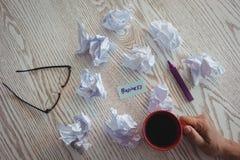 Mano de la empresaria que sostiene la taza de café por los papeles arrugados en el escritorio en oficina Imágenes de archivo libres de regalías