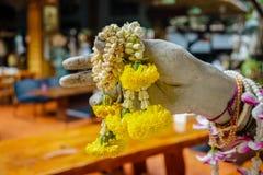 Mano de la estatua con las flores rituales Imagenes de archivo