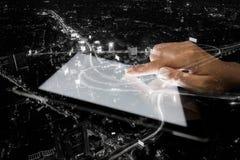 Mano de la exposición doble usando la tableta y ciudad el noche foto de archivo libre de regalías