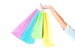 Mano de la hembra que sostiene bolsos de compras coloridos imagenes de archivo