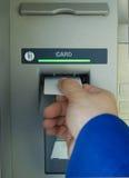 Mano de la máquina de efectivo y tarjeta en blanco Fotos de archivo libres de regalías