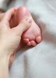 Mano de la madre que da masajes al pie del bebé encendido Fotografía de archivo libre de regalías