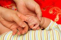 Mano de la madre y del padre y del bebé Fotografía de archivo