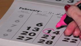Mano de la muchacha con drenaje rojo del marcador una forma del corazón en calendario el 14 de febrero almacen de video