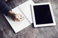 Mano de la muchacha con el lápiz, el diario en blanco y la tableta digital en un woode Fotos de archivo libres de regalías