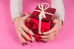 Mano de la muchacha con las cajas rojas del abrazo del suéter aisladas en fondo rosado Imagenes de archivo