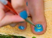 Mano de la muchacha del adolescente con pedicura del cepillo del laque del esmalte su pie de los dedos del pie Fotografía de archivo