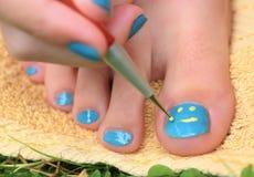 Mano de la muchacha del adolescente con pedicura del cepillo del laque del esmalte su pie de los dedos del pie Fotos de archivo