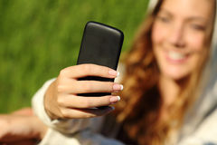 Mano de la muchacha del adolescente usando un teléfono elegante con su cara en el fondo Foto de archivo libre de regalías