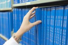 Mano de la muchacha del primer que selecciona el libro de un estante Foto de archivo