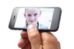 Mano de la muchacha del teléfono celular de foto