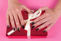 Mano de la muchacha en la caja de regalo roja con el arco blanco aislado en fondo rosado Fotografía de archivo libre de regalías