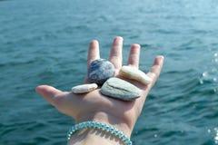 Mano de la muchacha por completo con las pequeñas piedras en la playa Fotografía de archivo