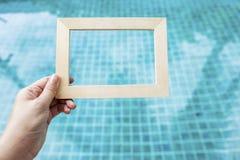 Mano de la muchacha que lleva a cabo el marco de madera Imagenes de archivo
