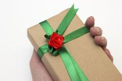 Mano de la muchacha que lleva a cabo un regalo de vacaciones embalado en papel y atado con una cinta verde con una flor roja de l fotos de archivo