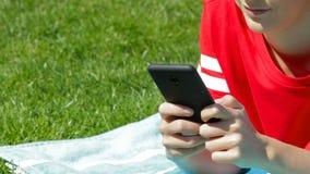 Mano de la muchacha que manda un SMS en el teléfono en la hierba
