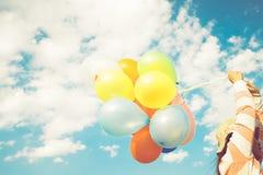 Mano de la muchacha que sostiene los globos multicolores hechos con un efecto retro del filtro del instagram imagenes de archivo