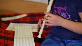 Mano de la muchacha que toca la flauta en casa almacen de video