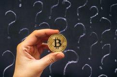 Mano de la mujer con Bitcoin de oro contra la pizarra con la pregunta Imágenes de archivo libres de regalías