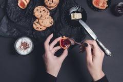 Mano de la mujer con el atasco y las galletas de la cuchara cerca de la taza de galletas del chocolate del café o del capuchino e Fotos de archivo libres de regalías