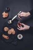 Mano de la mujer con el atasco y las galletas de la cuchara cerca de la taza de galletas del chocolate del café o del capuchino e Fotografía de archivo libre de regalías