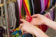 Mano de la mujer con el collar colorido en parada en el bazar Imagenes de archivo