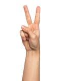 Mano de la mujer con el concepto de dos fingeres de victoria aislado en el fondo blanco imagen de archivo