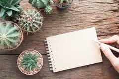 Mano de la mujer con el cuaderno en blanco en el escritorio que cultiva un huerto con el pla del cactus Foto de archivo libre de regalías