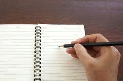 Mano de la mujer con el cuaderno negro de la escritura del lápiz en la tabla de madera Fotografía de archivo libre de regalías