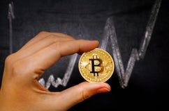 Mano de la mujer con el dinero virtual de Bitcoin contra la pizarra con el ch Imagenes de archivo