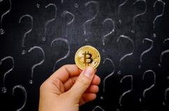 Mano de la mujer con el dinero virtual de oro de Bitcoin contra la pizarra Fotografía de archivo libre de regalías