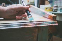 Mano de la mujer con el escritorio de madera de la pintura del cepillo con la pintura cretácea Imagen de archivo libre de regalías